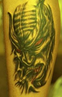 Evil demon tattoo on leg