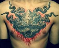 Frightful demon head tattoo on chest