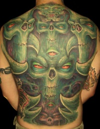Green monsters with red eyes tattoo on whole back