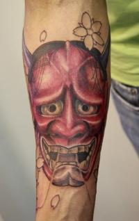 Red demon tattoo on arm